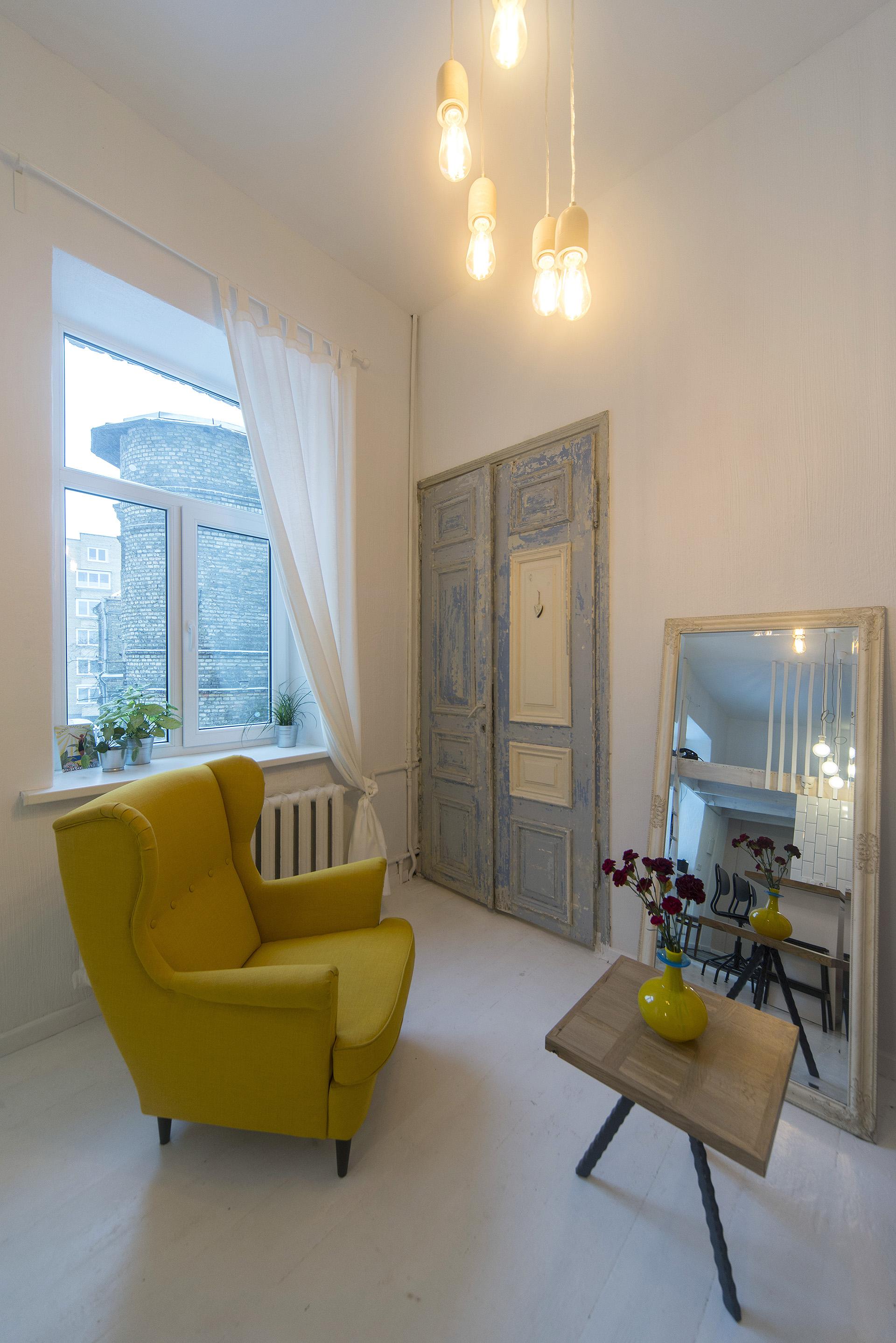 svetaine-interjeras-baltas-renovuota-aukštos-lubos-fotelis
