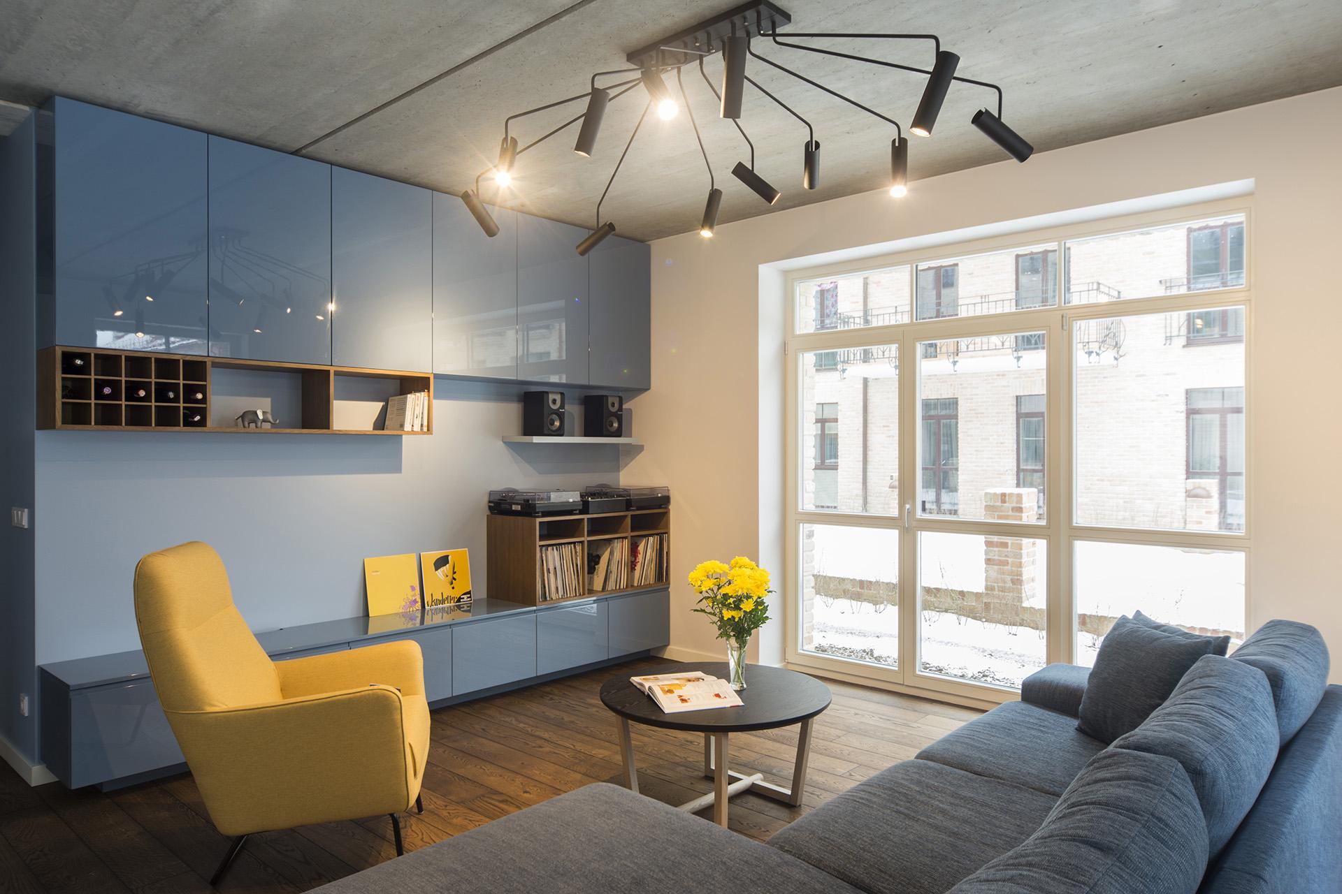 Svetainė-mėlyna-šviestuvas-industrinis-betono-lubos-moderni
